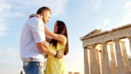 Beautiful Greek Couple embrace with historical Greek architecture int he background. video