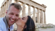 Beautiful Greek couple takes a selfie with historical Greek architecture in the background. video