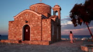 Beautiful Greek woman walking near old church, looking at amazing seascape video