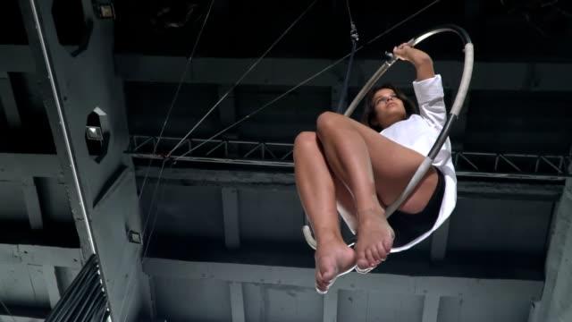 Beautiful gymnast sways in the aerial hoop in slowmotion video