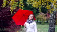 Beautiful happy girl with red umbrella at autumn park during fall leaves. 1920x1080 video