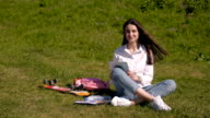 Beautiful Happy Smiling Brunette Using Tablet PC Sitting In Park On a Sunny Day video