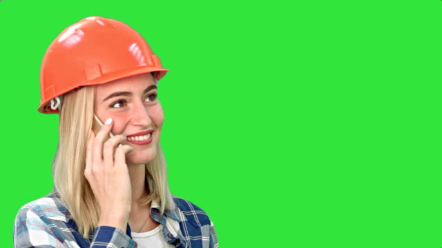 Beautiful happy woman in orange hardhat have a phone call via smartphone and smiling on a Green Screen, Chroma Key video