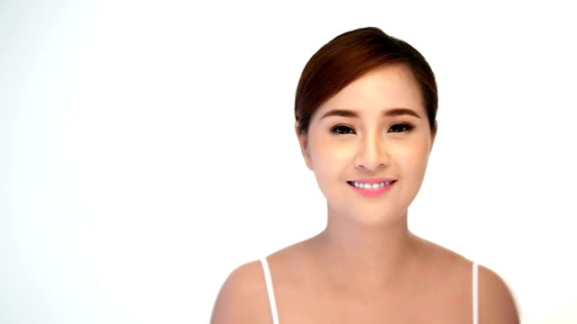 Beautiful healthy smiling woman with fresh skin of face over white background. video
