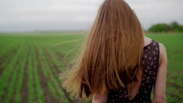 Beautiful healthy woman in dark dress with floral print stands in green field and wind blowing her hair video
