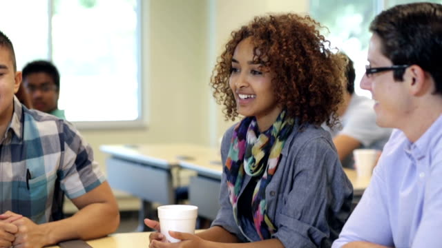 Beautiful high school student talking with study group in classroom video