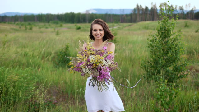 Beautiful inspired woman holds a bouquet of wildflowers video
