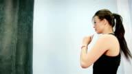 Beautiful Kickboxing women training punching bag in fitness studio fierce strength fit body slow motion kickboxer series, Beautiful brunette video