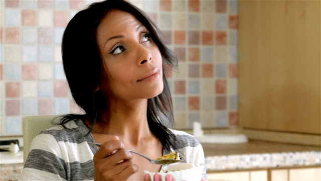 Beautiful lady eating cereals at home video