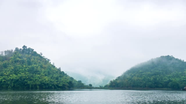 Beautiful Lake in front of Twin mountains with fog and storm cloud, Time lapse video