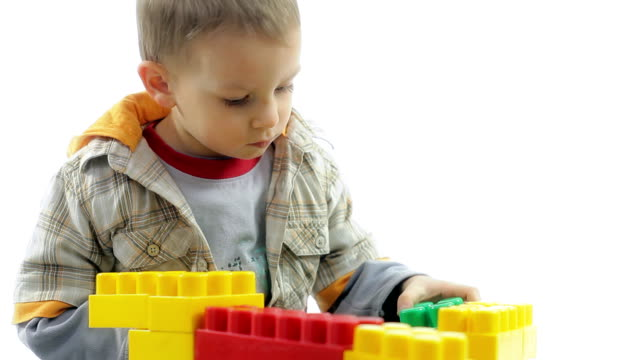 Beautiful little boy playing with color blocks. video