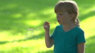 Beautiful little girl blows bubbles video