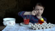 Beautiful little girl paints eggs for Easter, red and yellow video