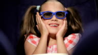 Beautiful little girl waching movie in the cinema video