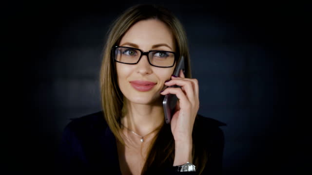 Beautiful long-haired boss woman is standing in her office and speaking on the phone with dark grey wall in the background. Female executive manager is working remotely using digital gadget video