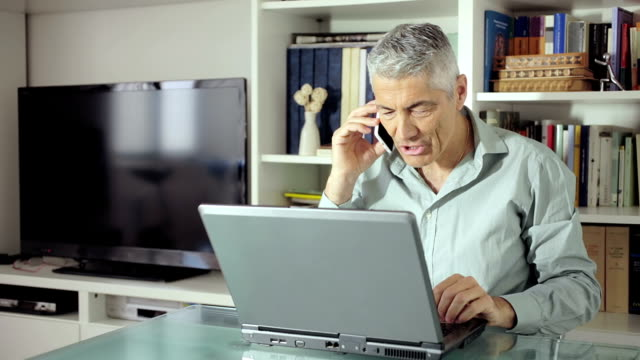 beautiful man using computer at home and responding at the phone: smartphone video