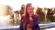 Beautiful model girl looking at camera in sunset. video