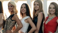Beautiful models in dresses posing near the columns on a street video