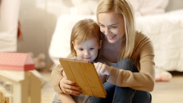 Beautiful Mother and Her Little Daughter Have Good Time Reading Children's Books on a Tablet Computer. Children's Room is full of Toys. video