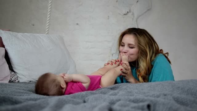 Beautiful mother kissing newborn baby's feet video