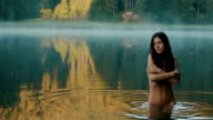 Beautiful naked seductive witch in the carpathian lake. Breathtaking moment of harmony with nature. Mythological concept video