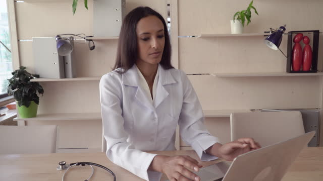Beautiful nurse sits at the wooden desk with laptop video