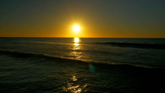 AERIAL: Beautiful ocean waves sparkling in golden sunset sun video