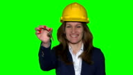 Beautiful realtor business woman with helmet hold new house construction keys. video