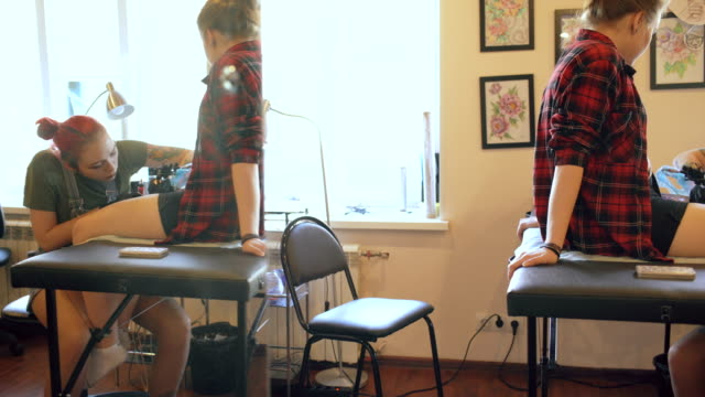 Beautiful red haired woman tattoo artist tattooing picture on leg of young girl client in studio video