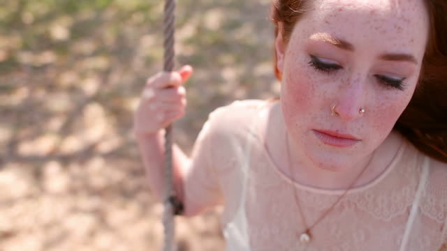 Beautiful Redhead sits on a swing in a park video