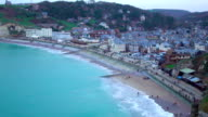 Beautiful resort town on the ocean shore, people walking on beach and embankment video