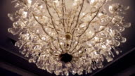Beautiful retro luxury crystal strass chandelier isolated on a white wall of the restaurant. video