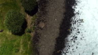 AERIAL: Beautiful rocky and stony wild beach by restless emerald ocean video