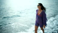 Beautiful romantic woman walking on the beach in summer vacation. video