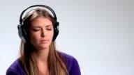 Beautiful sad pensive young woman in headphones video