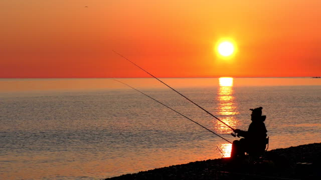 Beautiful scene with fishermen silhouettes with rod sitting on sea beach video