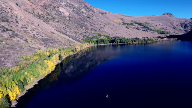 Beautiful scenic of a lake in the wilderness with fishermen fishing in the morning sun. video