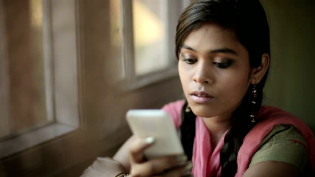 Beautiful serene Indian girl reading SMS sitting near window. video