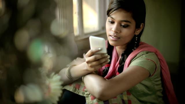 Beautiful serene Indian girl reading SMS sitting near window. video