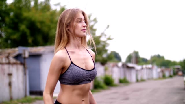 Beautiful sexy athletic young blond woman in top, shorts, engaged in gym, performs various strength exercises with dumbbells, near the old abandoned garages video