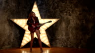 Beautiful sexy girl playing electric guitar in the music hall video