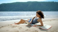 A beautiful sexy young lady is laying at a beach using laptop video