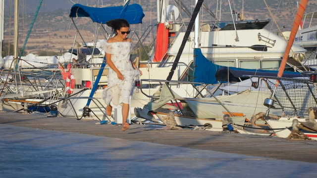 Beautiful sexy young woman wearing long white dress running at a port next to the boats video