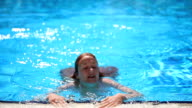 Beautiful slim girl with red hair floats in the pool and smiles. video