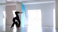 Beautiful slim gymnast trains in dancing class to prepare for trainings video