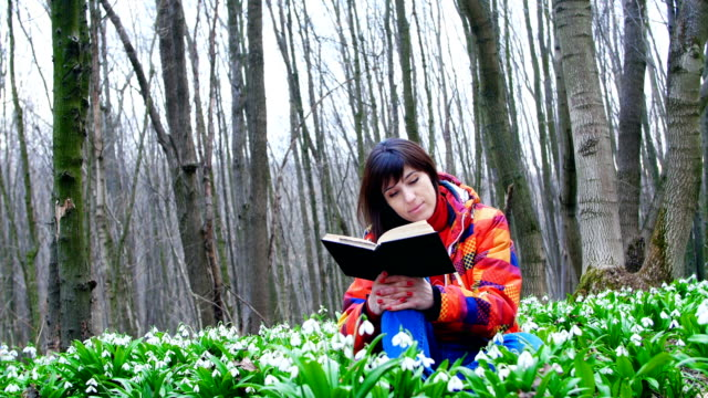 A beautiful smart girl is reading an interesting book in a spring forest full of blossoming snowdrops video