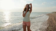 Beautiful smiling girl quickly walking on the sea water along the seashore in summer video