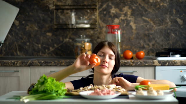 beautiful smiling woman cook play with vegetables on table in kitchen at home video
