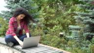 Beautiful student using laptop in campus garden video