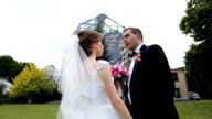 Beautiful stylish newlywed couple posing with pink bridal bouquet in botanic garden, glass structure background video